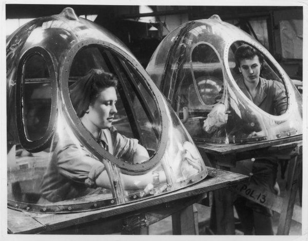 Two women polish aircraft gun turrets