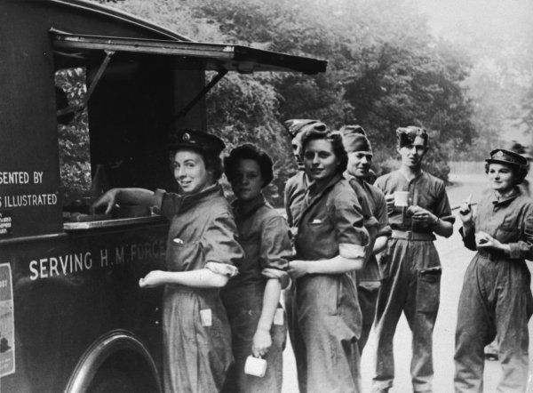 Members of the A.T.S. in overalls queue up for refreshments during a work break