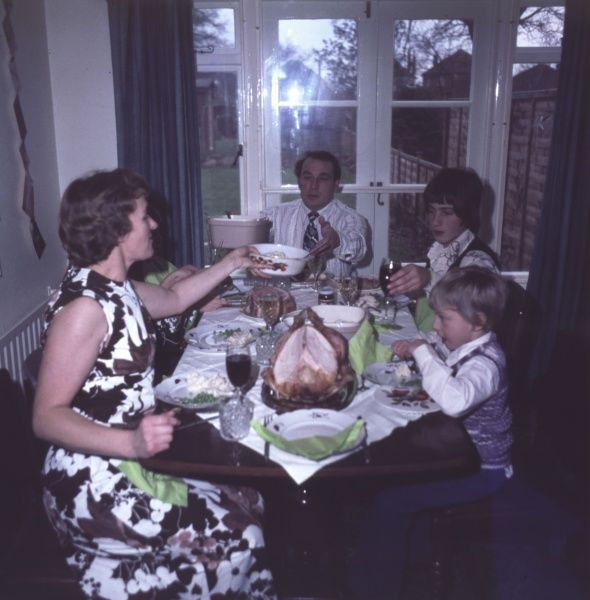 A traditional Christmas meal with the mother and father and two young boys in tank tops, turkey, wine and all the trimmings. Date: 1975