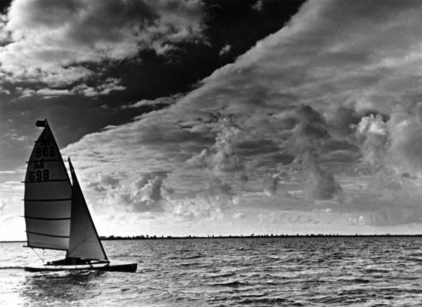 A yacht takes to the open seas, with a dramatic cloud formation in the skies above. Date: 1930s
