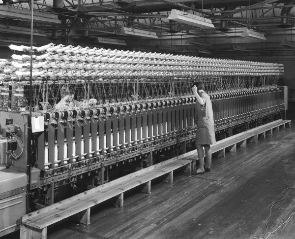 A lady working at a complex multi-level machine for rolling yarn onto circular spools, after the wool has been industrially spun, at Patons & Baldwins factory in Darlington. Patons & Baldwins was a leading British manufacturer of knitting yarn