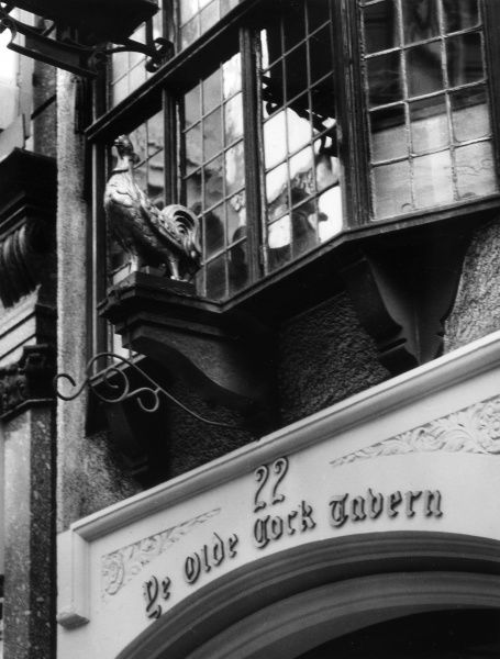 The sign above the entrance to 'Ye Olde Cock Tavern', a famous old hostelery on the Strand, central London. Date: 1960s