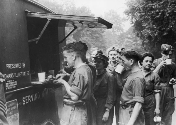 "Troops and other war workers, both men and women, enjoy a cuppa in the queue for the YMCA ""Tea Car"", which served food and drink to them and those bombed from their homes"