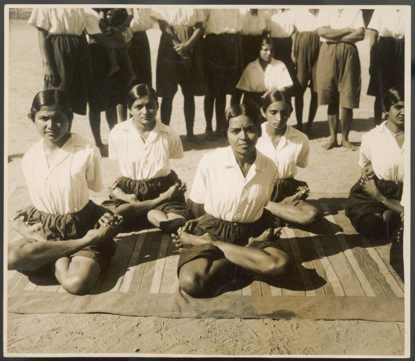 A group of Indian girls, yoga apprentices. While squatting in this position, they must control their breathing and concentrate upon a perfect balance of mind and body. Date: 1930s