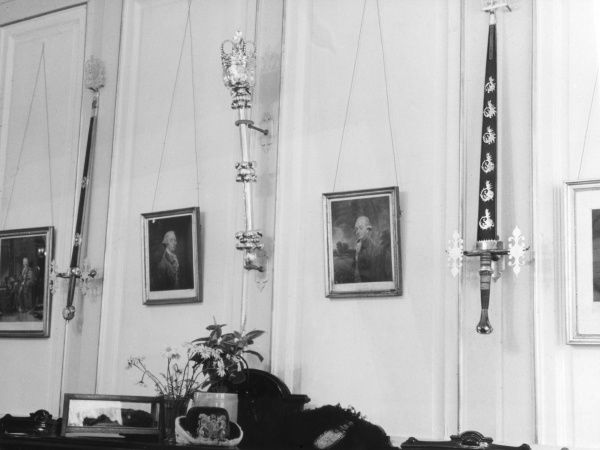 Some of the treasures of York Mansion House : The wall of the dining room, showing some swords, paintings and a mace. Date: 1950s
