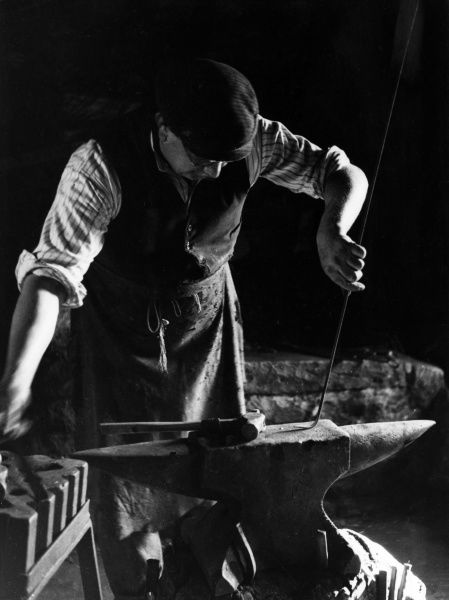 The Smithy (blacksmith) at work at his anvil in Dent, Yorkshire, England. Date: 1930s