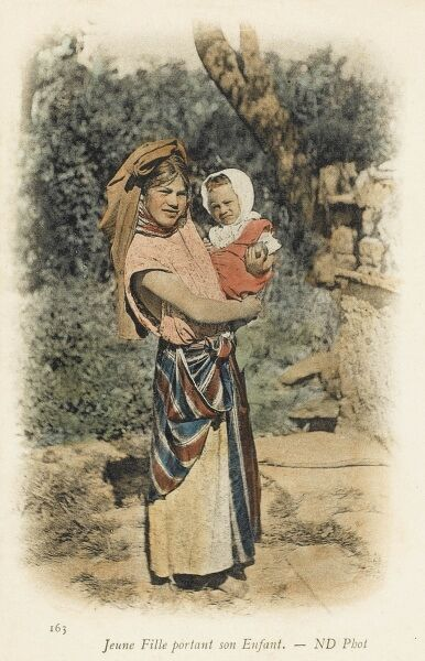 A young Algerian girl carrying her baby