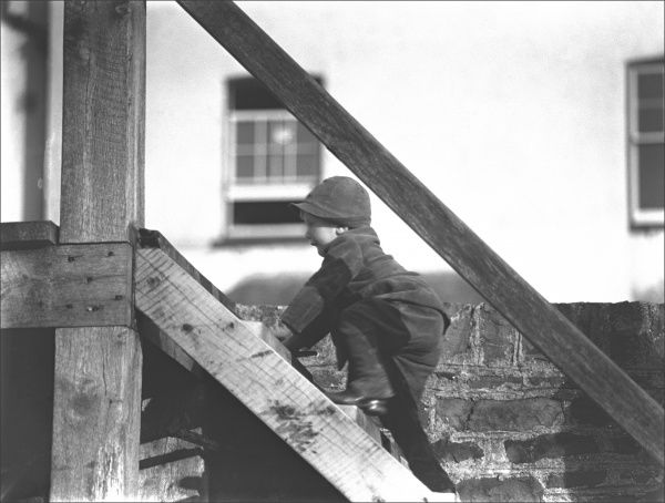 A young boy climbing the wooden steps up from the beach to the seafront. Photograph by Ralph Ponsonby Watts