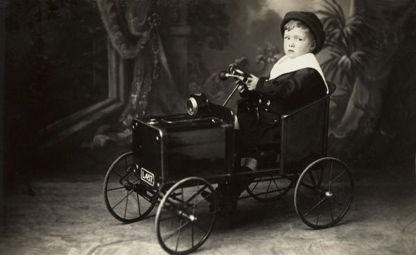 A young boy in a toy car poses for his picture in a photographic studio. The miniature vehicle has a slender steering wheel, horn and number plate