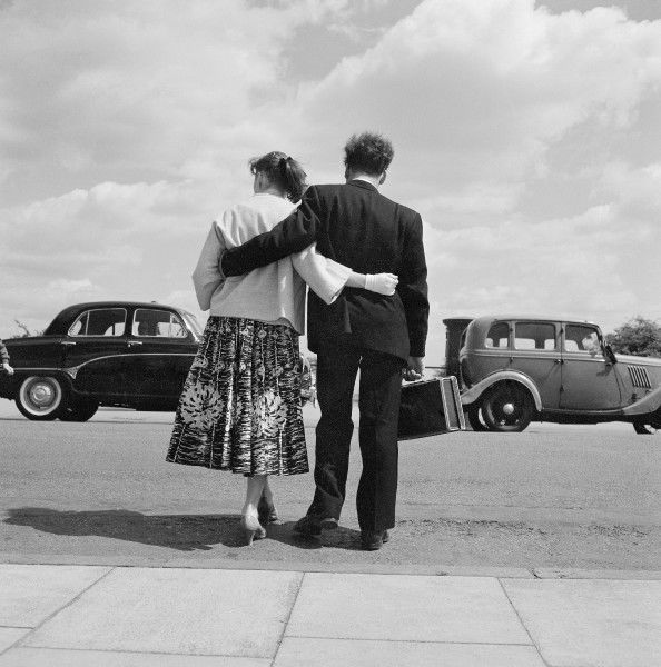 Rear view of a young couple standing with arms around each other at the side of an unidentified road in Hampstead, probably near Waterstone pond Hampstead, London