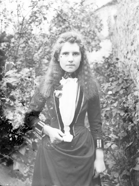 A young Edwardian woman with long wavy hair in a garden, Mid Wales