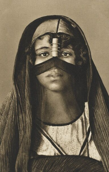 A striking young Egyptian woman in traditional headdress