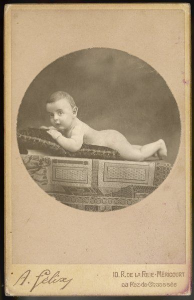 A very young Frenchman lies on a cushion