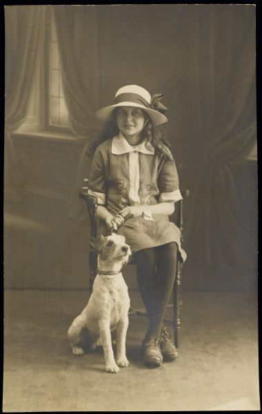 A happy looking little girl wearing a hat, poses for her studio portrait with her pet dog, probably a Fox Terrier