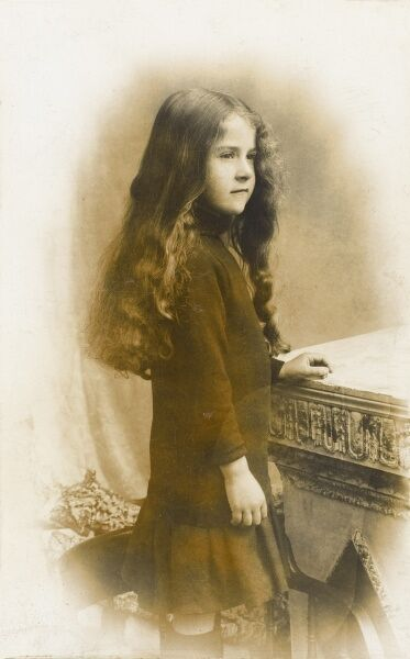 A fabulous photographic postcard of a young girl, barely into her teens with extraordinary long brown, slightly wavy hair, resting against a stone table