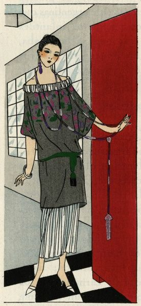 Young lady answering the door in a grey and white crepe outfit by Paul Poiret. The tunic has a pink and green design, and there is a matching green belt slung low on the hips