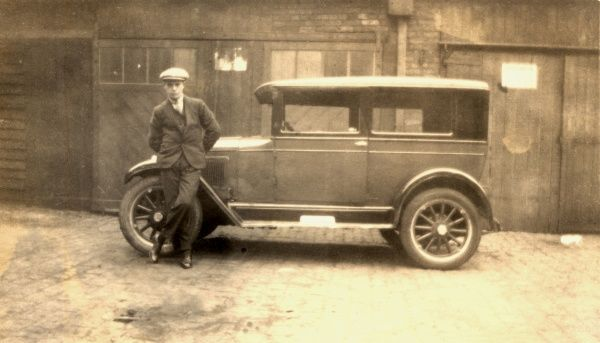 A young man stands cooly against the bonnet of his car with legs crossed in a jaunty fashion, in front of a row of wooden garages