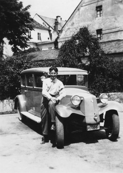 A young man poses for his photograph perching on the front of a car. He is probably from Vienna or South Moravia (now in Czechoslovakia)