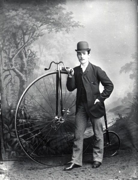 A young man and his pennyfarthing bicycle, posing against a painted backdrop in the photographer's studio in Haverfordwest, Pembrokeshire, Dyfed, South Wales