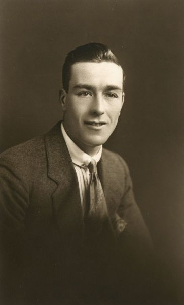 A young man in a smart jacket, collar and tie, poses for his photograph in the studio. Date: circa 1930s