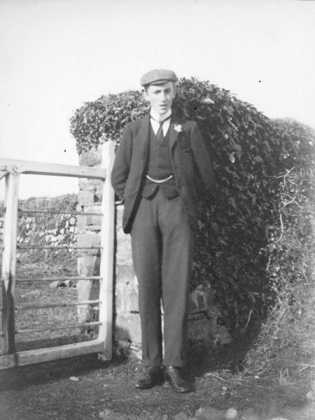 A young Edwardian man in a smart suit and flat cap, standing by a gate. He has a watch chain across his waistcoat and a flower in his buttonhole