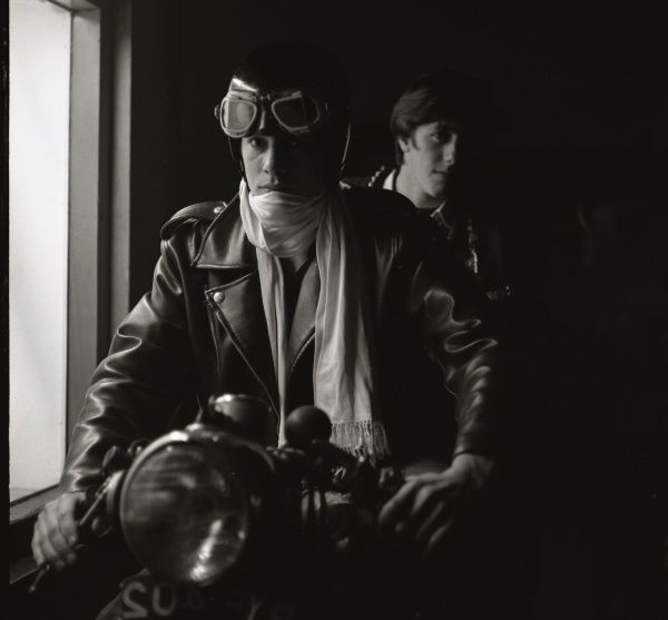 Two young men sitting on a motorcycle. The one nearest the camera is wearing leather jacket, scarf, and a helmet with goggles