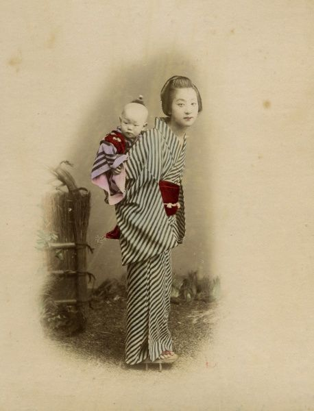 Young Japanese nurse carrying a baby