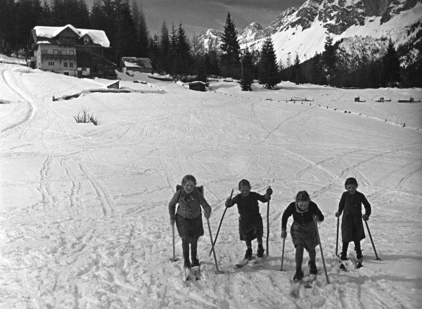 Four children learning to ski. Date: 1930s