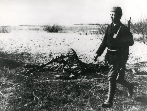 A 14-year-old soldier, Peter Vucinie, on his way to the trenches in Serbia on the eastern front during the First World War. Behind him is the skeleton of a horse. Date: 1915-1917
