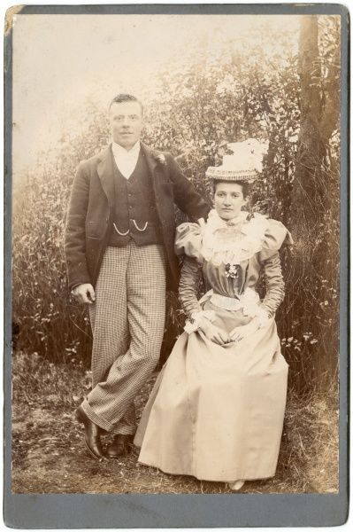 A young Victorian couple pose for their photograph in an outdoor setting. They are wearing their best clothes, perhaps attending a wedding