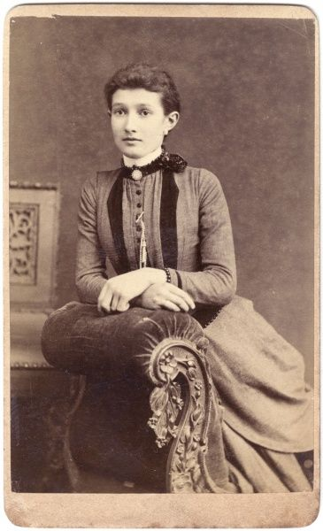 A young Victorian woman poses for her photograph in the studio, sitting on an ornate chaise longue. She is wearing a dress with a high collar, and buttons at the front