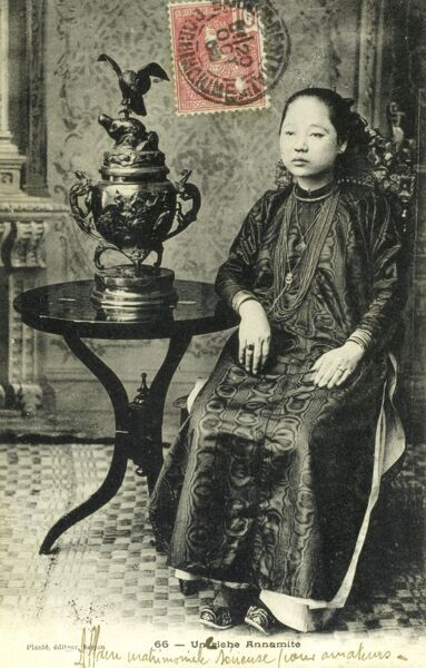A rather seriously-looking young woman from the Annam region of Vietnam. Date: 1903