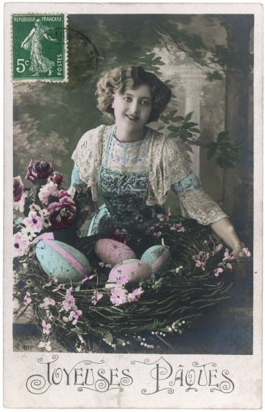 A young woman in a garden with a basket full of large Easter eggs decorated in pink and blue
