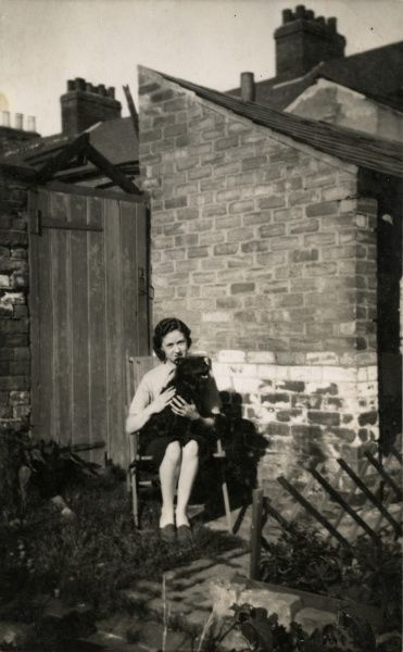 A young woman sitting in a deckchair in a back garden with a dog on her lap. Date: circa 1930s