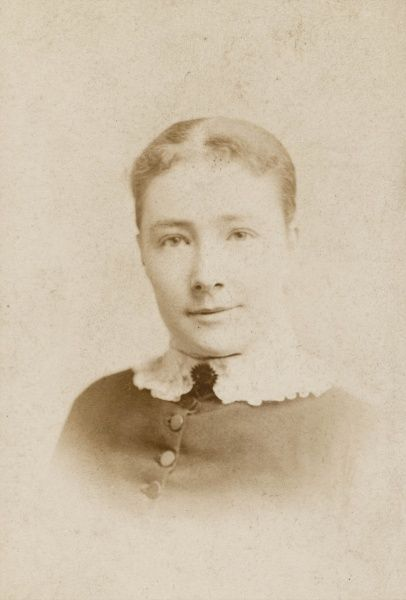 A young woman in a head and shoulders photograph, wearing a buttoned dress with a white collar