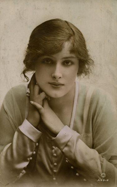 A young woman (the actress Peggy Kurton) in a demure pose with her hands clasped at her neck. Date: early 20th century