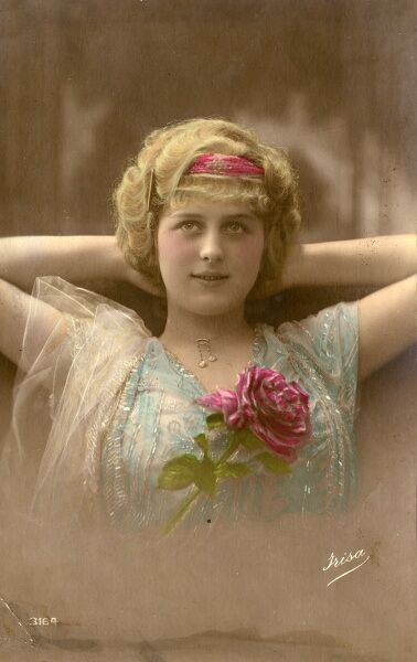 A young woman with blonde hair on a postcard, sitting in a relaxed pose with her hands behind her head