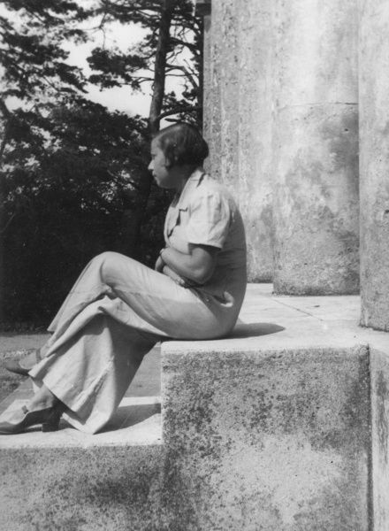 A young woman sitting on a step wearing wide-legged trousers, which were fashionable during the 1940s