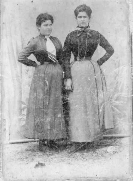 Two young women, probably sisters, pose for their photograph in a studio. They are probably from the settlement of Kostel (also known as Podivin) in South Moravia, now in Czechoslovakia