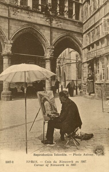 A street artist painting in a corner of the Nieuwerk annex of the Cloth Guild Hall, a huge flemish gothic structure era in Ypres, Belgium. This beautiful historic city was devastated during World War One and much of the Cloth Hall was destroyed