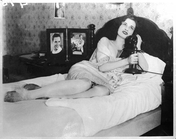 Yvonne La Bois, American starlet, reclining languidly on her bed as she makes a phone call, surrounded by photographs of her men friends