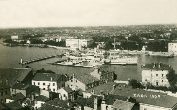 A panoramic view looking over Zadar (Zara) - Croatia - showing the harbour, where an impressive white steamship has docked, alongside a row of white submarines - possibly part of the Croatian (Yugoslavian) navy?