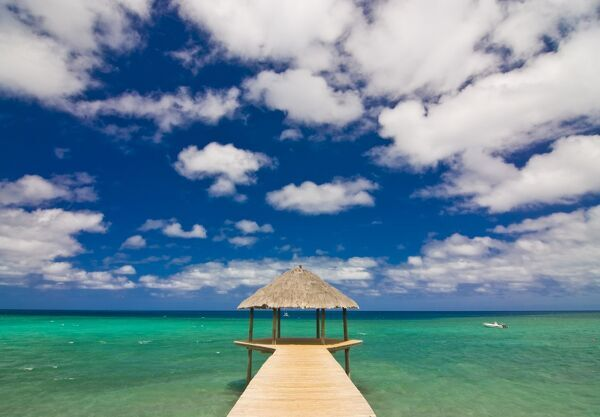 covered pier in the turquoise water of the indian ocean on the beach of longoni