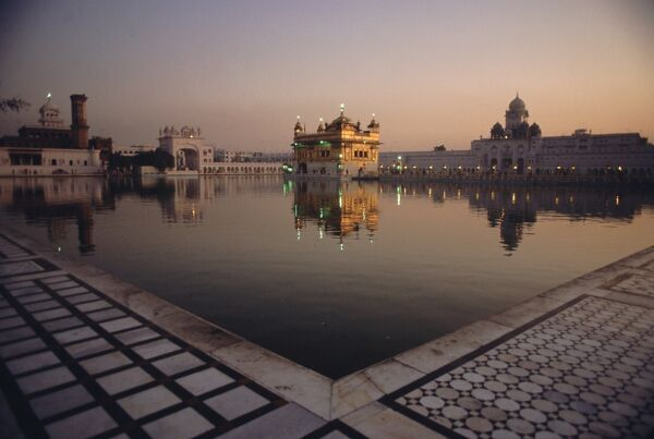 Dawn at the Golden Temple and cloisters and the Holy Pool of Nectar, sacred site of the Sikh religion, Amritsar, Punjab State, India, Asia