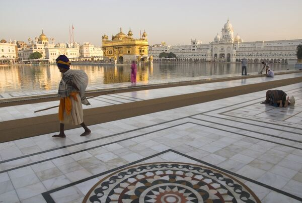 Elderly Sikh pilgrim with bundle and stick walking around holy pool, Golden Temple, Amritsar, Punjab state, India, Asia