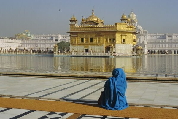 A pilgrim in blue sits by the Holy Pool of Nectar at the Golden Temple, centre of the Sikh religion, Amritsar, Punjab, India