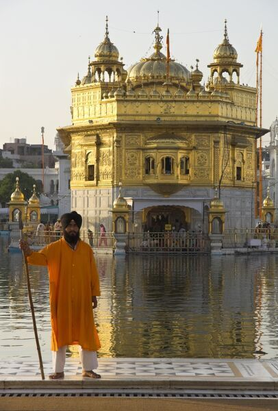 Shrine guard in orange clothes holding lance standing by pool in front of the Golden Temple, Amritsar, Punjab, India, Asia