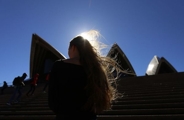 A woman stands in front of the Sydney Opera House during windy weather in Sydney, Saturday, July 13, 2019. (AAP Image/Steven Saphore)