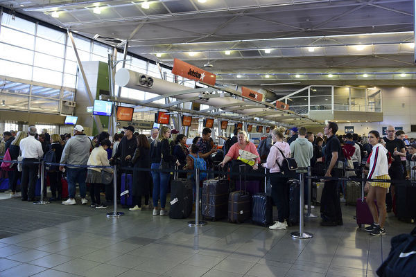 People are seen lining up at the Jetstar bag drop desks in the domestic departures terminal at Sydney Airport, Sydney, Saturday, July 13, 2019. Hundreds of flights in and out of Sydney airport have been delayed or cancelled due to the wild weather