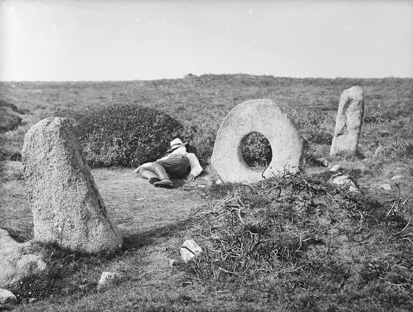 A general view of Men-an-Tol (the holed stone) with a reclining man to the left of it, and two standing stones. Photographer: Herbert Hughes